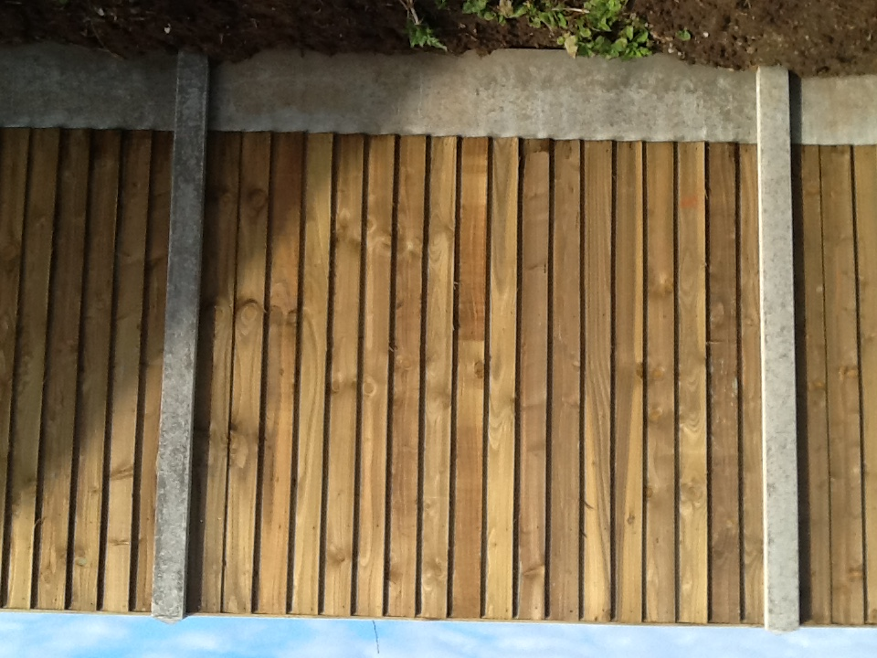 Closeboard garden fence installation with concrete kickboards and posts